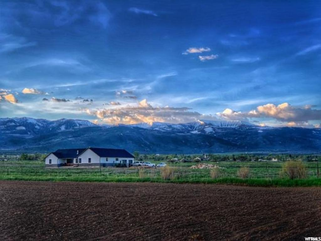 Brand NEW home with great room open floor plan and a large den and mudroom on a 38-acre horse/hay ranchette with well water, Rocky Mountain Power and 1,000 gal buried propane tank that you own for gas. Subdividable and it currently has 3 parcel numbers. Great views of the mountains from every window and the porches. 18 shares of Horseshoe irrigation and 1-acre-ft well water right. About 4 acres is pressurized with a hand line. 60 tons of hay on the 1st cutting 2019. 2 new fields of 9 acres planted in the spring of 2019 should produce an additional 15 to 20 tons. New fields are pasture grass, excellent for horses. Other fields are alfalfa/grass mixture. 37 acres in green belt. Two water heaters, the basement is plumbed for a bath and you can frame the rest as you wish - 3 or 4 bedrooms would not be a problem, cold storage, built-in double size fridge and freezer, humidifier on furnace, intercom and garage has two separate single doors for more room. MLS map is correct. Google Earth & Maps are 39.501771, -111.501002 Buyer to verify all information. Must have 24 hr notice for showings.