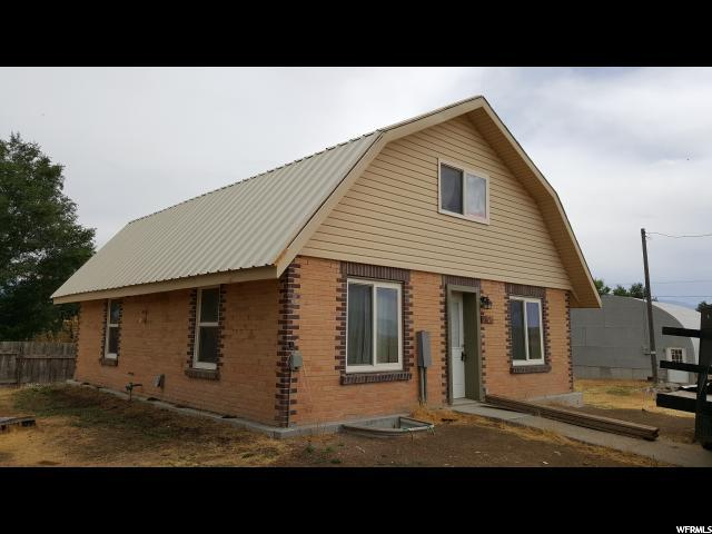 Huge price reduction!! Cute updated house in Moroni on 1.66 acres w/mother in law apartment. Brand new carpet and laminate, upstairs and down. Beautiful new cupboards and countertops in both kitchens. Open top floor that could be used as a master bedroom. Basement mother-in-law apartment or can be rented out for extra income. Brand new metal roof. Includes large metal garage which has a service pit. 20 x 14 foot garage door. Home was completely remodeled in 2005 and more was done in 2017 due to a water leak. All new fresh water copper lines. All new waste and drainage lines to septic tank. New electric lines with 200 Amp service. Natural gas upgrade with larger lines for when gas becomes available. Propane lines from tank upgraded. Two hot water heaters, one is propane, the other electric which is new. Garage and house have 200 amp service. Septic tank has been cleaned and line was leached 8 years ago. Range and dryer hookups are gas and electric. A brand new Kinetico water filtration system has been installed. Buyer and buyer's agent to verify all information.