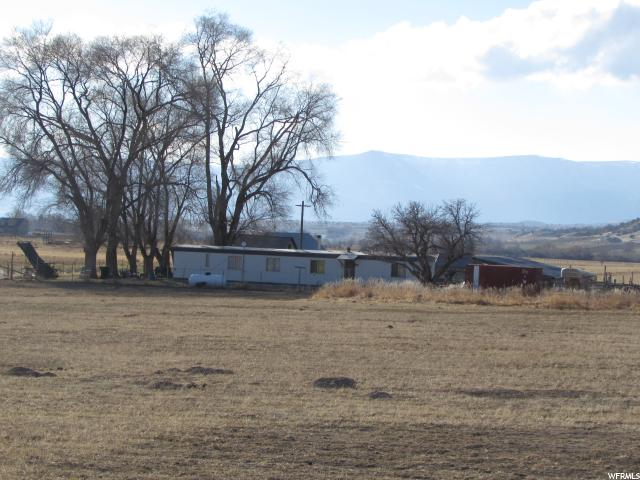 GENTLEMENS RANCH! Great opportunity to build your dream home in the country while living on the property. Includes irrigated hay field, sub-irrigated pastures, milk barn & other outbuildings. Includes State Water Right 65-129 & 23.5 shares of Pleasant Creek Irrigation Co. stock. Oil, gas & mineral rights excluded.