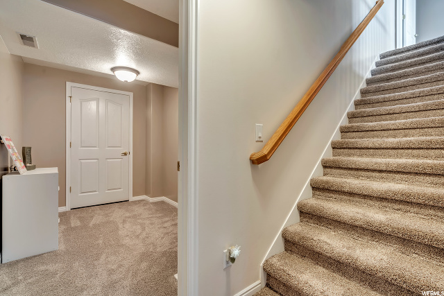 Stairs down from Main Level to Basement: View is into a play room area that allows access to the Storage room and Cold Storage and Door 1 of 2 into the unfinished basement space.