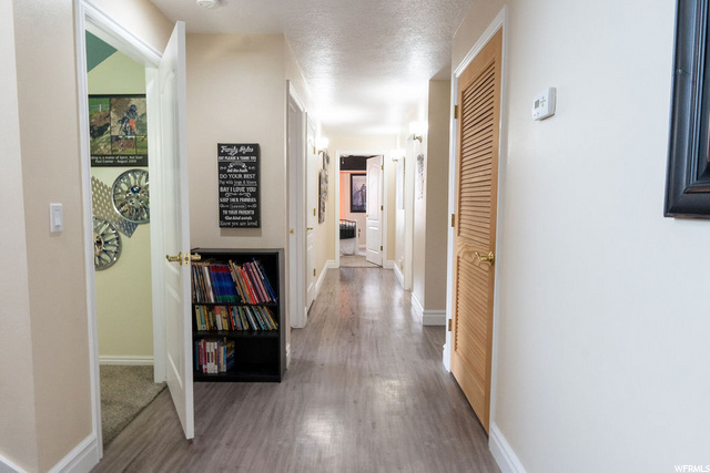 Basement Hallway leading to bedrooms on the North Side of home. Door on left - under-stairs room, wood door on right - utility room w/ humidifier, air purifier, water softener, tank-less water heater and storage
