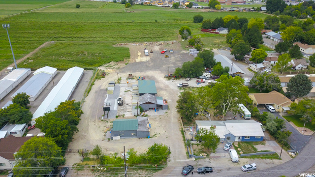 UNBELIEVABLE PROPERTY -  5.46 Acres!!  Front Parcel #26-031-0063 (.75 Acres) is zoned R-1/ light industrial.  Parcel # 26-028-0051 (4.73 Acres) in back (larger parcel  see photos) is zoned as agricultural.  Springville City is open to rezoning.  There are 8 water shares and a.015 CFS  well.  The house and farmhouse are currently being rented out to 3 parties with a total income over $4000 a month!  Property includes the additional acreage and outbuildings.